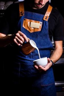 Бариста наливает молоко в кофе
