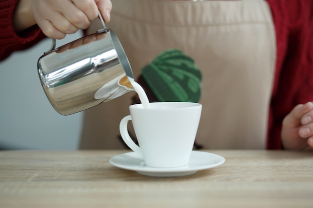 Barista pours milke from steel pot to white cup with coffee
