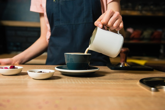 Barista pours out milk from pitcher