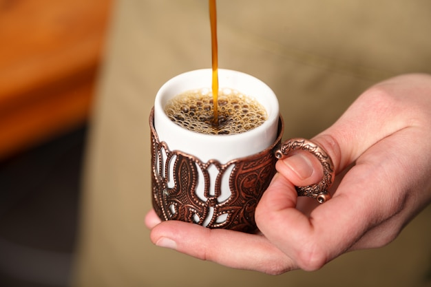 Barista pours turkish coffee into a traditional embossed metal copper cup, close-up, selective focus.
