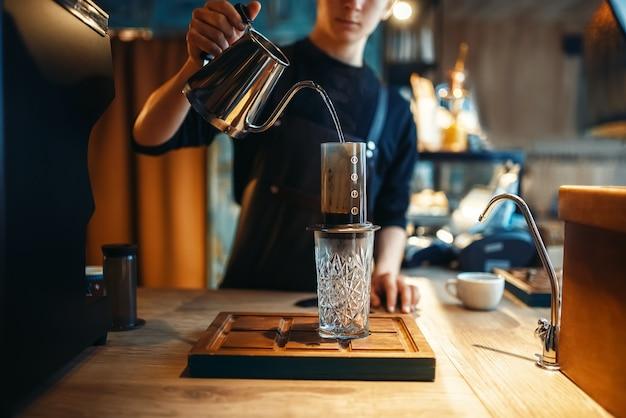 Бариста наливает воду из кофейника в стакан