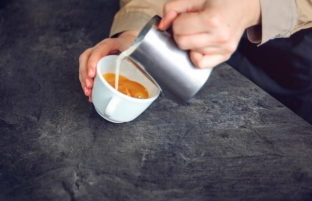 바리 스타는 카푸치노 용 컵에 휘핑 우유를 붓습니다. 소프트 포커스.