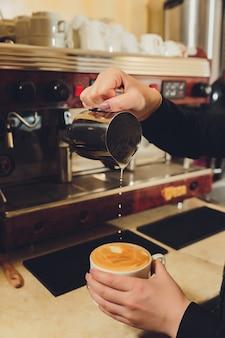 バリスタは彼のコーヒーショップでカプチーノを準備します