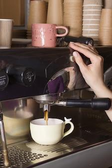 バリスタは小さなコーヒー ショップでコーヒーを準備します。