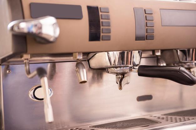 Barista prepares espresso in his coffee shop. close-up