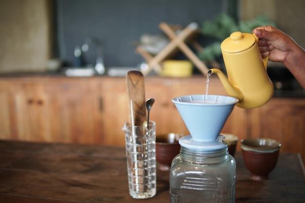 Бариста готовит заваривать кофе с кофеваркой и капельным чайником. капающий молотый кофе с фильтром