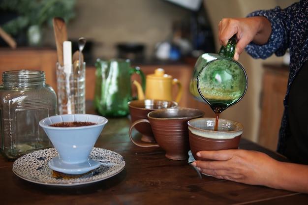 コーヒーメーカーとドリップケトルで淹れるコーヒーを準備するバリスタ。フィルターで挽いたコーヒーを滴下