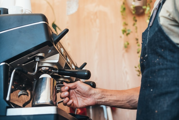 A barista preparing a cappuccino with a coffee machine