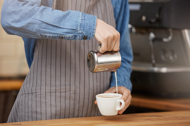 Barista preparing cup of latte for customer in coffee shop.
