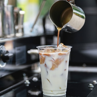 Barista preparing iced coffee. pouring coffee into the glass with milk and ice.
