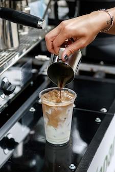 아이스 커피를 준비하는 바리 스타. 우유와 얼음으로 유리 잔에 커피를 붓습니다.