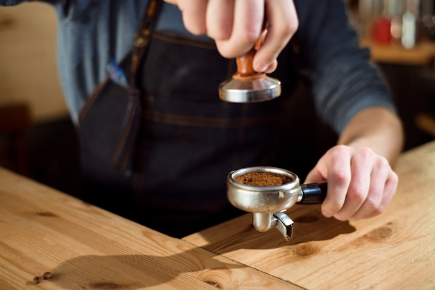 Barista presses ground coffee using tamper in a coffe shop