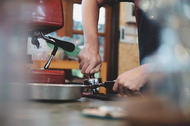 Barista pressing coffee in the machine holder.