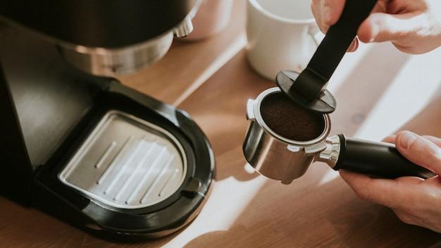 Barista pressing ground coffee in a coffee machine filter