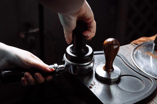 Бариста вдавливает молотый кофе в портофильтр.