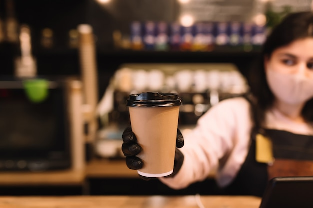 Barista in protective face mask and black gloves gives cup of coffee in cafe.