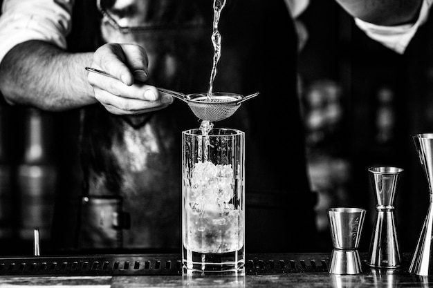 Barista putting alcohol into a cocktail glass with syrup and ice cubes.