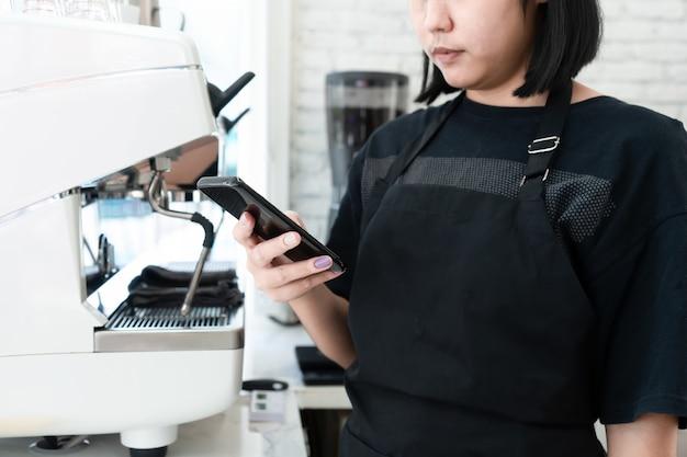 Бариста получает заказы на кофе от смартфонов в кафе. концепции малого бизнеса