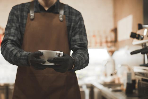 앞치마에있는 바리 스타의 남자는 커피 머신 근처의 아늑한 카페에 서서 커피 한 잔을 가지고 있습니다.