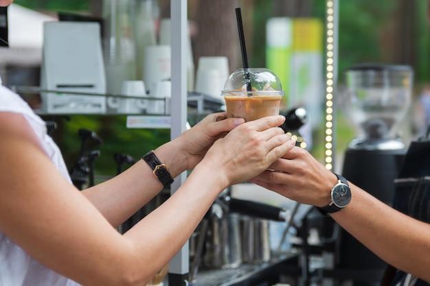 아이스 라떼와 함께 플라스틱 잔을 고객에게 판매하는 바리 스타