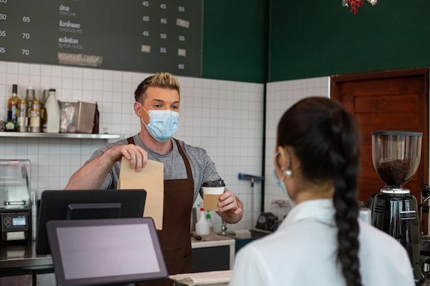 Бариста отправляет клиенту кофе и еду. предлагает новый нормальный образ жизни на вынос. напиток на утренний завтрак.