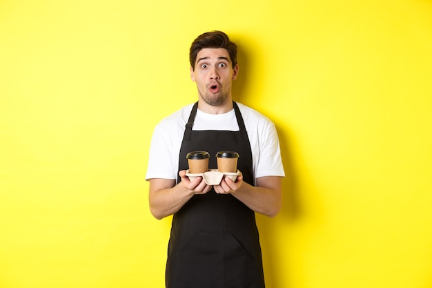 Barista serving coffee, looking surprised at camera, wearing black apron, standing against yellow background.