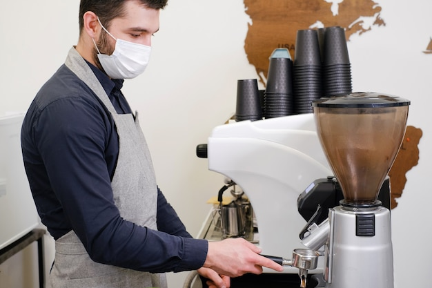 Barista serving coffee in takeaway cups in coffee shop in mask