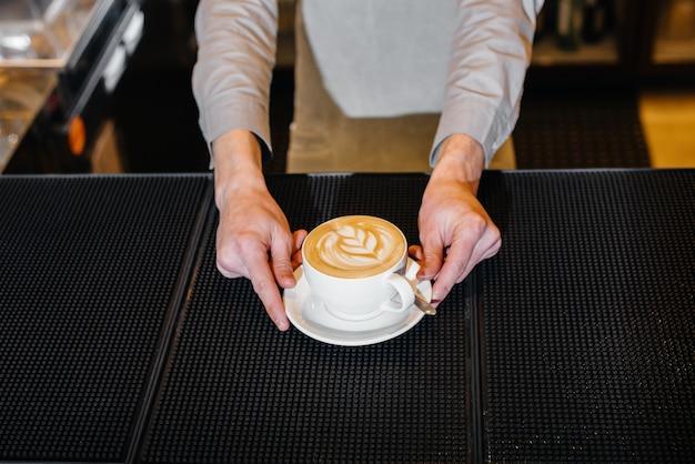 おいしいナチュラルコーヒーのクローズアップを提供するバリスタ。おいしいコーヒーのクローズアップ。