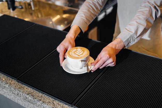 おいしいナチュラルコーヒーのクローズアップを提供するバリスタ