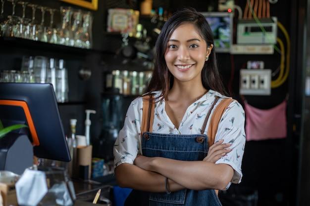 バリスタは笑顔でコーヒーショップのカウンターでコーヒーマシンを使用しています