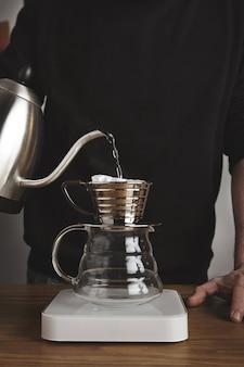 바리 스타는 뜨거운 물을 흘려 현대적인 주전자에서 여과 된 커피를 준비하고 흰색의 단순한 무게로 아름다운 투명한 드립 커피 메이커로 만듭니다.