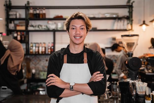 彼女の仕事でコーヒーショップの前に交差した手で立っているバリスタ