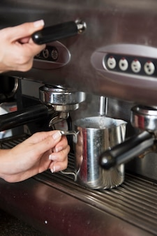 Barista taking hot water from tap in the mug