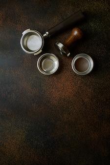 バリスタツール、バスケットセット付きのポルタフィルター、テキスト用のスペースのある暗い背景のコーヒー用テンパー、フラットレイ