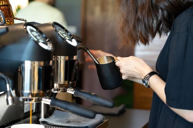 Бариста использует кофемолку для приготовления капучино.