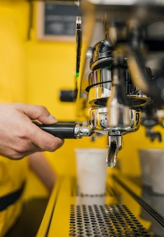 Barista using coffee machine in shop
