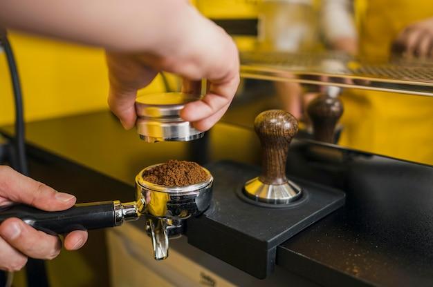 Бариста с помощью чашки для кофемашины
