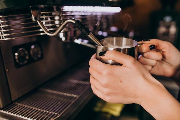 コーヒーマシンでコーヒーを暖めるバリスタ