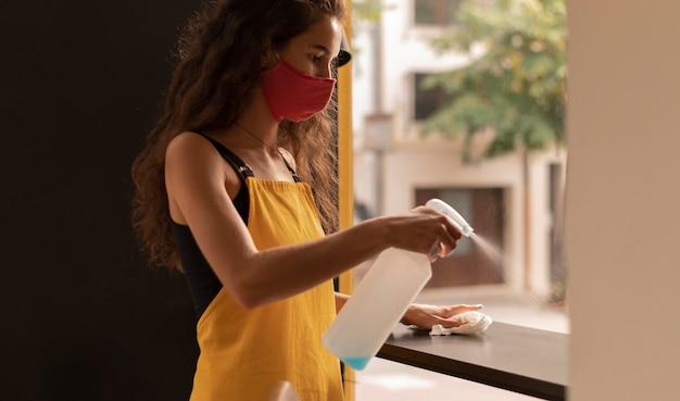 커피 숍에서 청소하는 동안 마스크를 쓰고있는 바리 스타