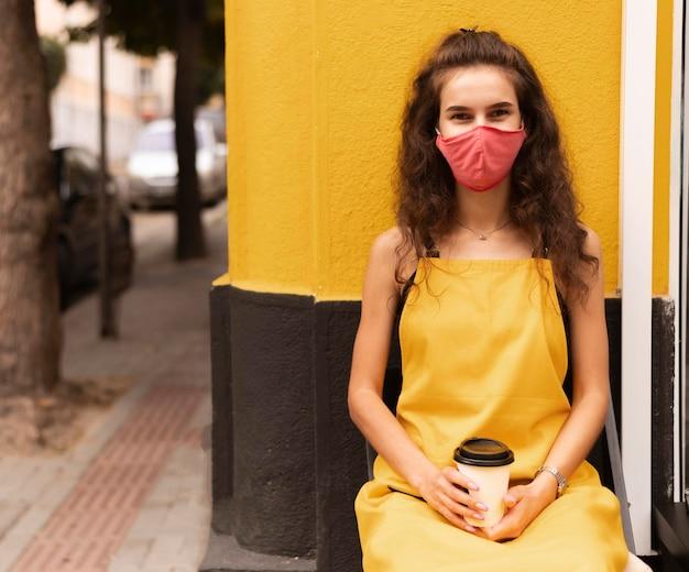 外で一杯のコーヒーを保持しながらフェイスマスクを身に着けているバリスタ