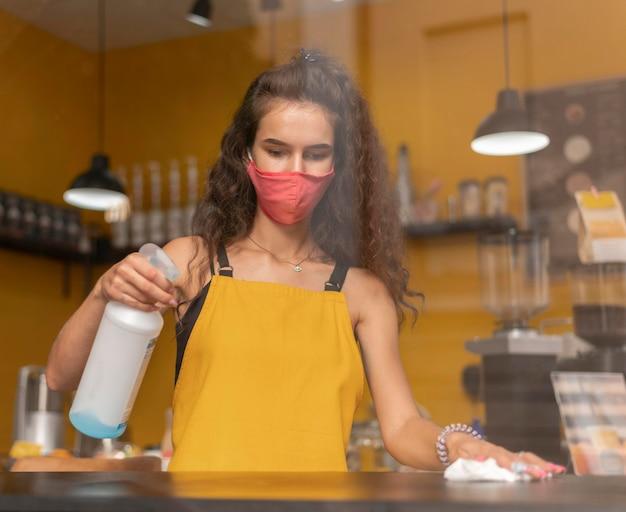 커피 숍에서 청소하는 동안 의료 마스크를 쓰고 바리 스타