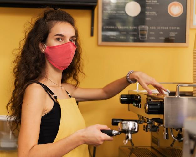 Бариста в медицинской маске во время приготовления кофе в помещении
