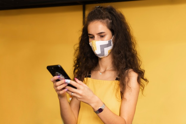 Barista wearing a medical mask while checking her phone