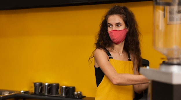 Barista wearing a medical mask with copy space