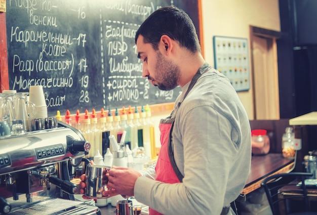 바리 스타는 아늑한 카페의 커피 머신에서 에스프레소 용 우유를 채찍질합니다.