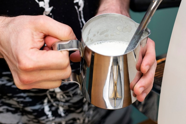 바리 스타가 커피 머신의 스팀으로 투수에 우유를 채찍질합니다.