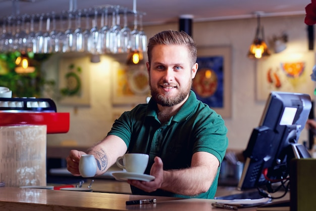 Barista with coffee cup in hand behind bar. welcome coffee shop