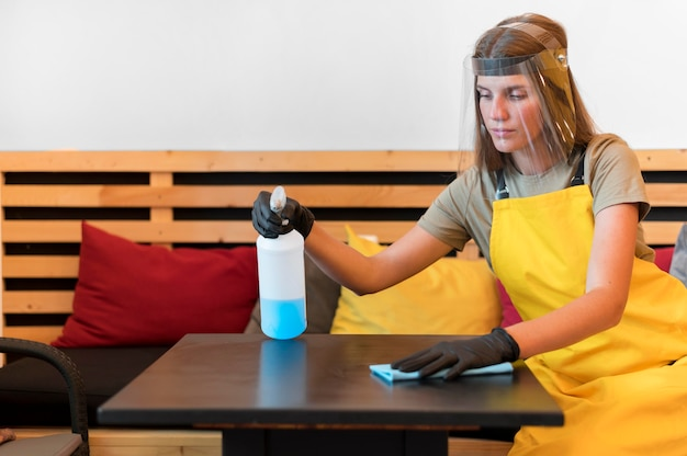 Barista with face protection and gloves cleaning tables