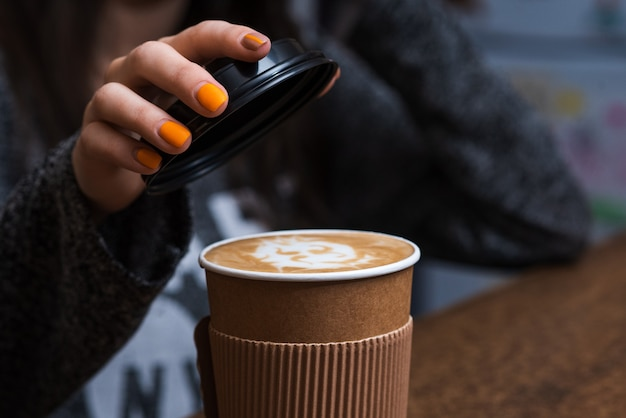 바리 스타 여성이 갓 만든 향기로운 커피로 일회용 유리 뚜껑을 닫습니다.