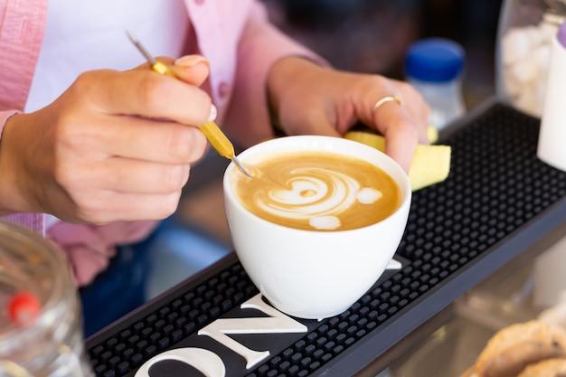 Бариста женщина рисует медведя на кофе пены в кафе. крупный план. латте арт.